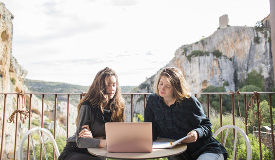 Spain, Alquezar, two women working together with laptop on terrace - AFVF00340
