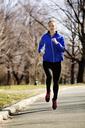 Woman jogging on road in park - CAVF11992