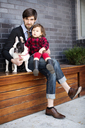 Portrait of father and daughter with dog sitting on bench against wall - CAVF12040