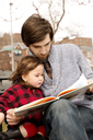 Father and daughter looking at book while sitting on bench in park - CAVF12058