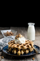 Close-up of waffles by milk garnished with whipped cream and walnuts - CAVF12253