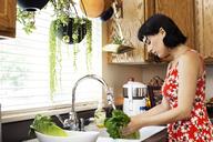 Side view of woman washing lettuce in kitchen sink - CAVF12271