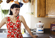 Smiling woman standing at kitchen counter in home - CAVF12274