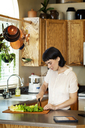 Smiling woman cutting fresh vegetables while standing at kitchen in home - CAVF12277