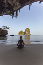 Rear view of woman in bikini meditating at beach seen through cave - CAVF12424