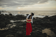Happy couple embracing while standing at beach against sky during sunset - CAVF12439