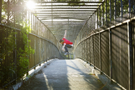 Man skateboarding on bridge - CAVF12454