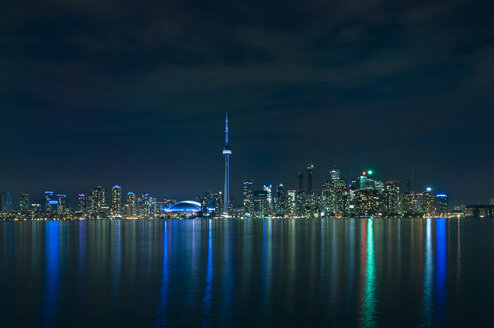 Illuminated modern buildings reflecting in lake Ontario against sky at night - CAVF12556