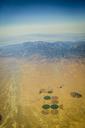 Aerial view of center pivot irrigation at desert against blue sky - CAVF12577