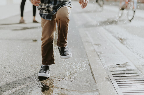 Low section of boy jumping on puddle at street - CAVF12616