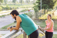 Happy man looking away while exercising at park with woman in background - CAVF12628