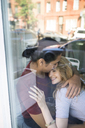 Couple embracing at restaurant seen through glass window - CAVF12676