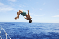 Full length of man diving into sea against sky on sunny day - CAVF12754