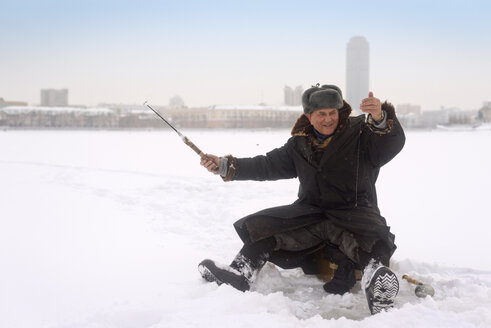 Happy man ice fishing in frozen lake - CAVF12769