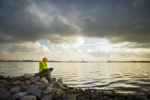 Woman sitting on rocks by lake against cloudy sky - CAVF12835