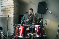Happy man playing drum kit at home - CAVF12868