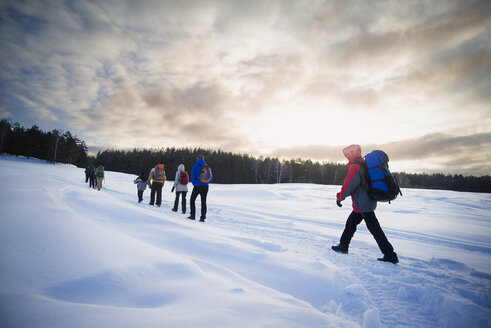 Friends hiking on snow covered field against cloudy sky - CAVF12880