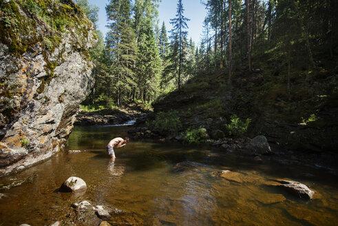 Man bending on river against trees - CAVF12922