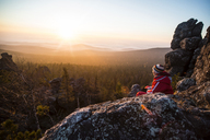 Woman sitting on rocks at mountain against sky at sunset - CAVF12979