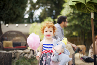 Portrait of girl holding candy floss and stuffed toy while standing at backyard - CAVF13147
