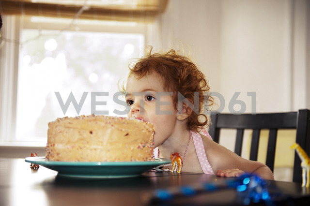 Girl having cake while sitting on table at home - CAVF13150