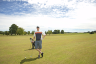 Happy man standing at golf course against sky - CAVF13192