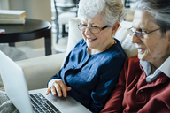 Senior couple using laptop computer in living room - CAVF13231