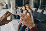 Cropped hands of senior man photographing family through smart phone on porch - CAVF13249