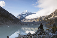 Rear view of hiker sitting at lakeshore against cloudy sky at Mt Cook National Park - CAVF13312