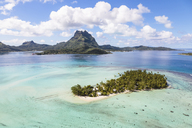 Scenic view of Bora Bora island against cloudy sky during sunny day - CAVF13336