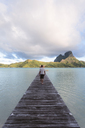 Rear view of man walking on jetty over lagoon against cloudy sky - CAVF13342