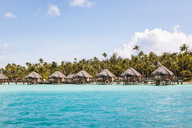 Stilt houses in lagoon of Bora Bora island against sky - CAVF13348