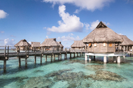 Stilt houses in lagoon of Bora Bora island sky during sunny day - CAVF13351