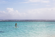 Rear view of woman paddleboarding in lagoon against sky - CAVF13369