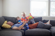 Father enjoying with sons while lying on sofa at home - CAVF13483