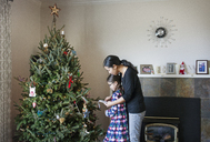 Side view of woman with daughter decorating Christmas tree at home - CAVF13537