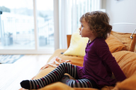 Girl looking away while sitting on sofa at home - CAVF13576