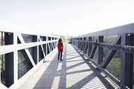 Rear view of boy standing on footbridge against clear sky during sunny day - CAVF13651