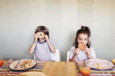 Brothers having breakfast while sitting against wall at home - CAVF13672