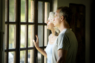 Thoughtful senior couple looking through window while standing at home - CAVF13711