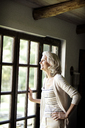 Smiling senior woman looking through window while standing at home - CAVF13717