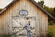 Rear view of father carrying son while playing basketball outside barn - CAVF13753