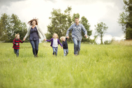 Happy family enjoying on grassy field - CAVF13765