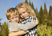 Portrait of siblings embracing at field on sunny day - CAVF13792
