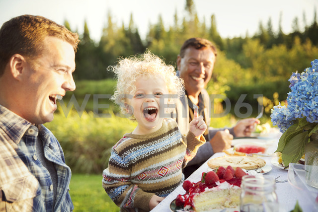 Cheerful family enjoying on picnic table - CAVF13813