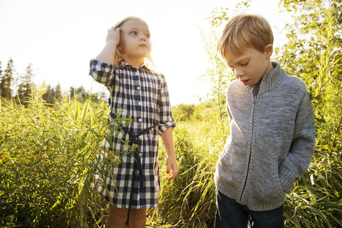 Siblings standing on grassy field - CAVF13819