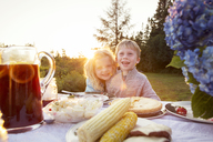Happy siblings by picnic table on sunny day - CAVF13825