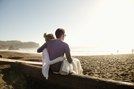 Rear view of couple sitting on wood at beach - CAVF13912
