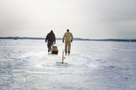 Rear view of friends walking on frozen lake against cloudy sky - CAVF13936