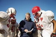 Coach sharing strategy to American football players standing on field - CAVF14005